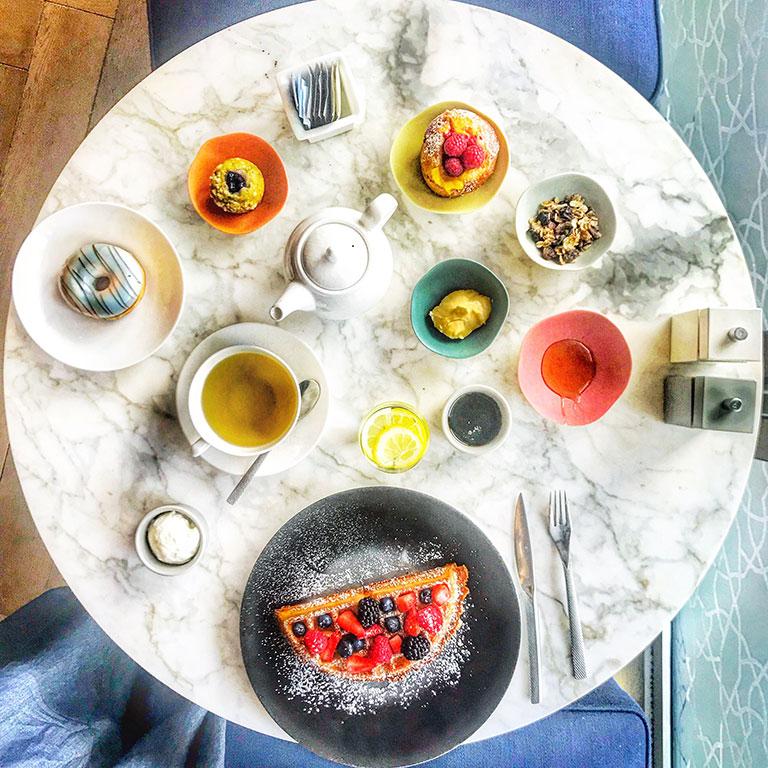 foto di un tavolo rotondo in marmo con la colazione di waffel succhi di frutta tè e pasticceria