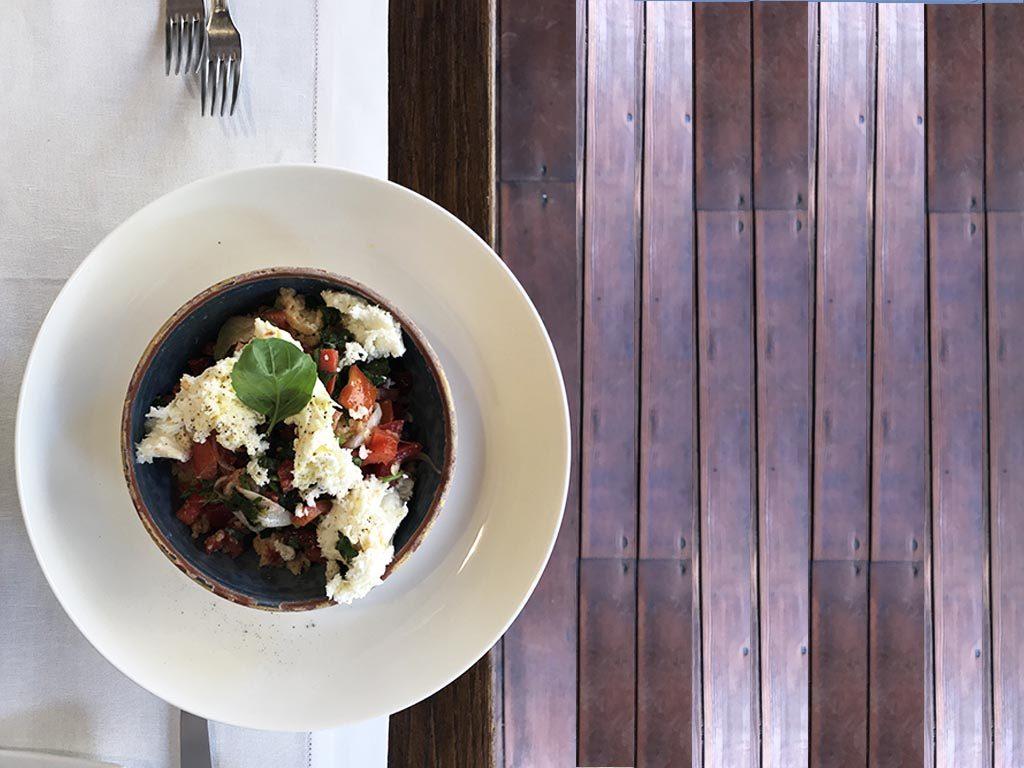 foto di un piatto di ceramica con  panzanella e stracciata di mozzarella