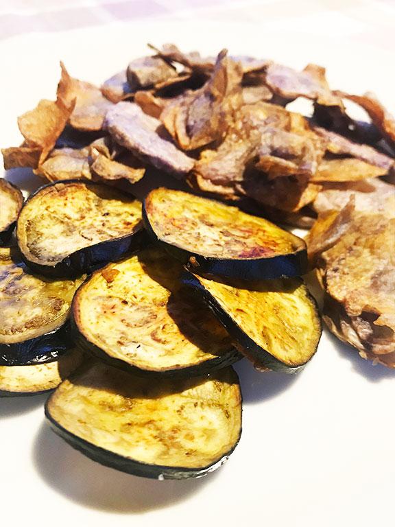 dettaglio di chips di melense fritte patate viola sullo sfondo servite su un piatto bianco