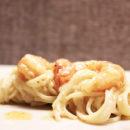 ciotola bianca con pasta caco e pepe con gamberi e foglia di cerfoglio