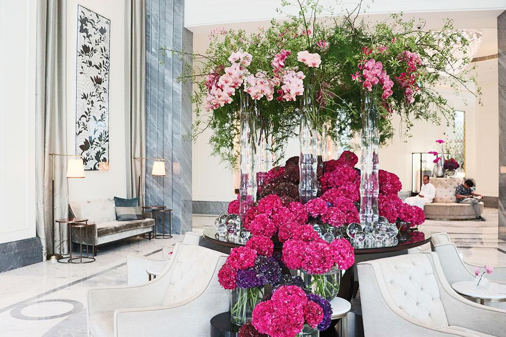 tavoli neri allestiti con vasi di cristallo ortensie fucsia fiori rosa e bianchi rami verdi