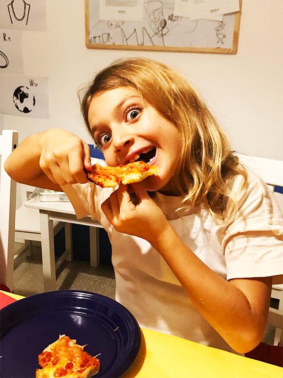 foto di una bambina che mangia pizza rossa
