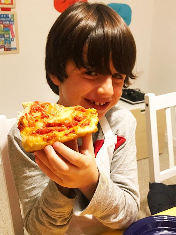 foto di un bambino che mangia la pizza rossa mentre sorride