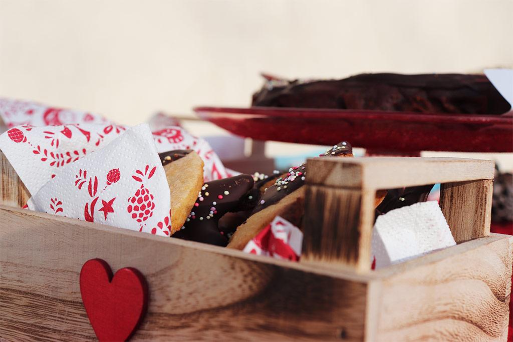 foto di una piccola cassetina in legno con un cuore rosso riempita con biscotti