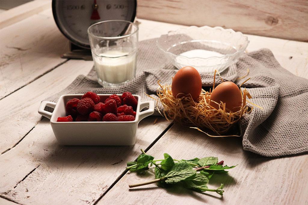 foto degli ingredienti per la mousse alla vaniglia, lamponi, uova, zucchero, panna, bilancia anni'50