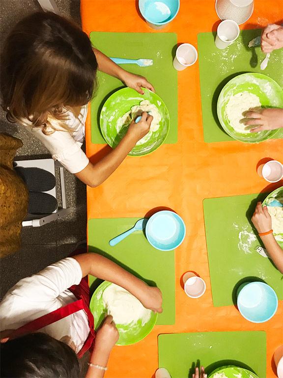foto di bambini che preparano la pizza